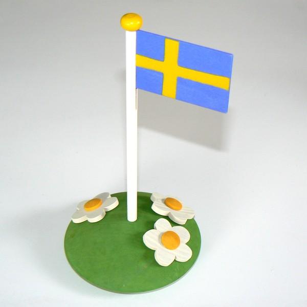 Sommerliche Tischdeko aus Holz: schwedische Flagge auf Blumenwiese